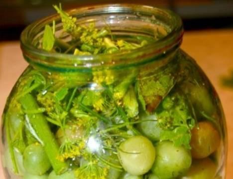 В стерилизованную банку кладем немного зелени, затем добавляем часть помидоров. снова кладем зелень, чеснок и перец.