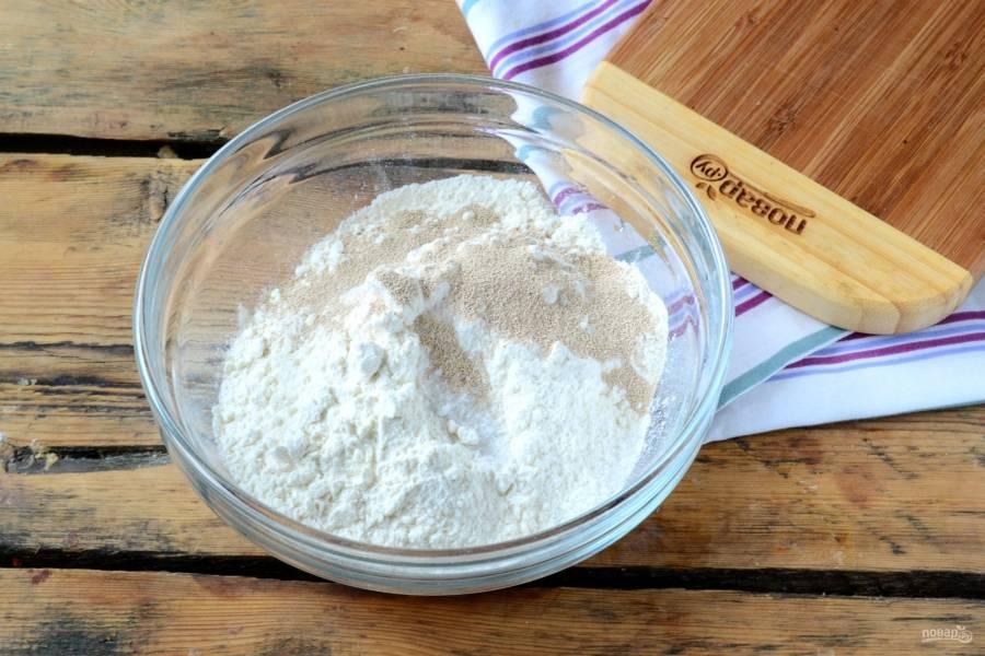 Для начала подготовьте тесто для бриошей. В миску просейте необходимое количество муки, добавьте остальные сыпучие ингредиенты: соль, сахар, дрожжи. Все перемешайте.
