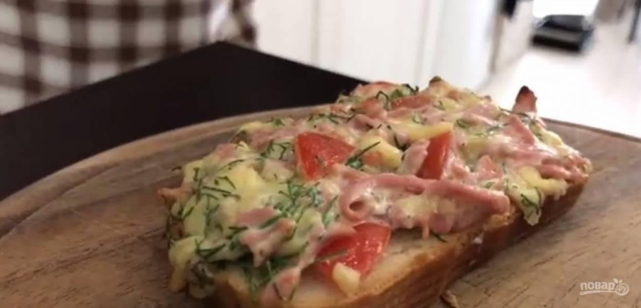 2. Майонез смешайте с чесноком и добавьте к начинке. Нанесите начинку на батон и отправьте в разогретую до 180 градусов духовку, чтобы расплавился сыр. Нарежьте лук, украсьте им горячие помидоры.