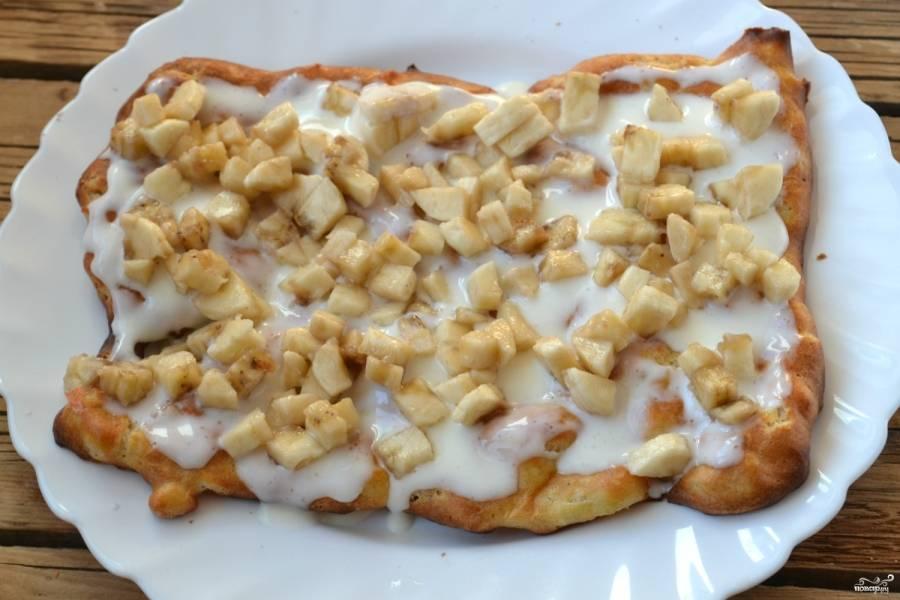На подходящую по размеру плоскую тарелку положите первый корж, обильно смажьте его сметанным кремом. Выложите сверху измельченные бананы.