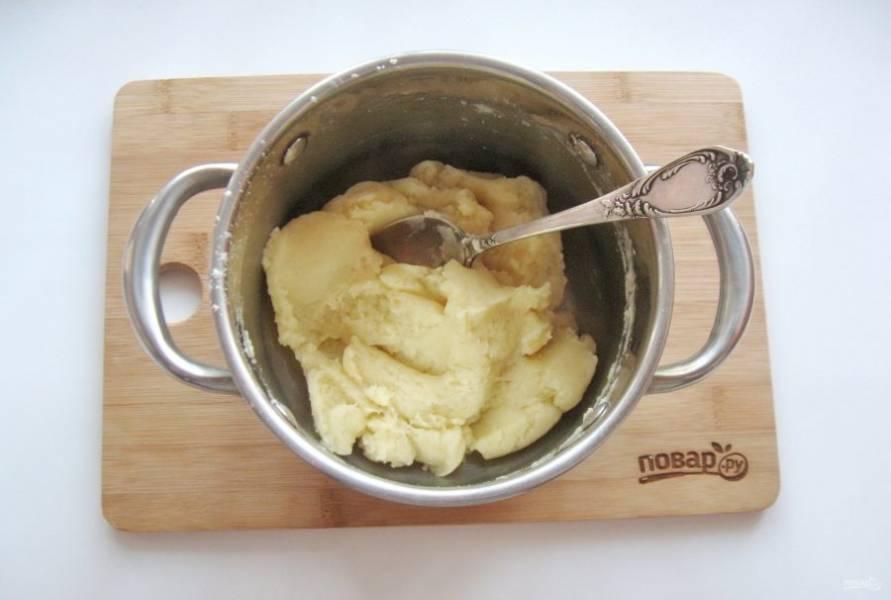Когда масло полностью растворится в горячей воде, всыпьте стакан муки. Постоянно перемешивайте, пока тесто не скатается в шар и начнет отставать от стенок кастрюли.