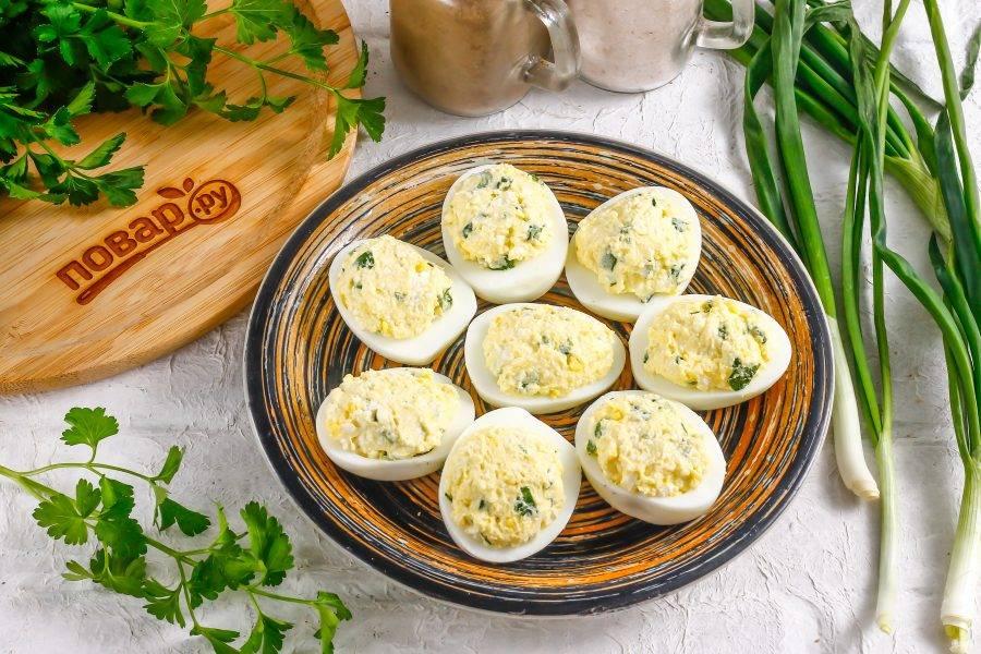 Нафаршируйте подготовленной начинкой лодочки из куриных белков на тарелке, выкладывая чуть выше.