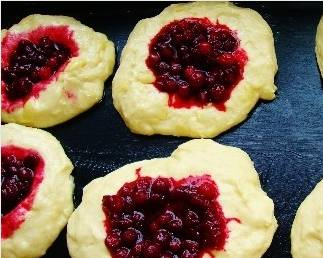 3. Тесто вымесим еще раз, лепим из него одинаковые кругляши. Бруснику тем временем перемешаем с сахаром и подогреем, чтобы ягоды были в сиропе. Выкладываем поверх кругляшей.