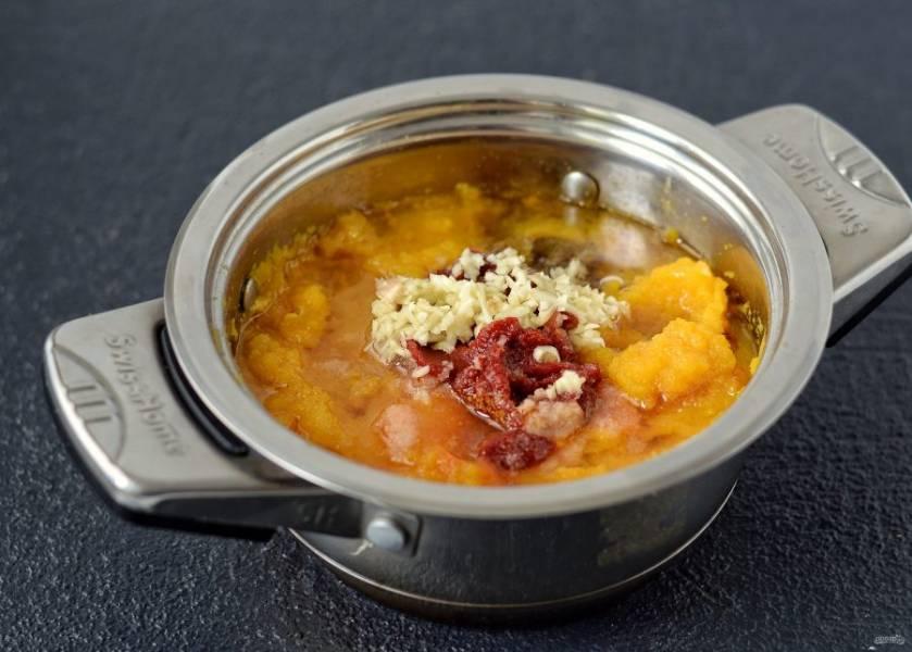 Добавьте в кастрюлю томатное пюре, оба вида перцев, растительное масло, лавровый лист, сахар и соль. Чеснок пропустите через пресс. Перемешайте, продолжайте варить ещё 30 минут.
