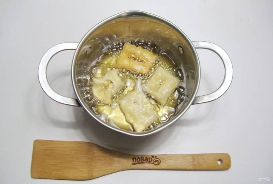 Хорошо разогрейте масло в кастрюле и выложите квадраты теста.