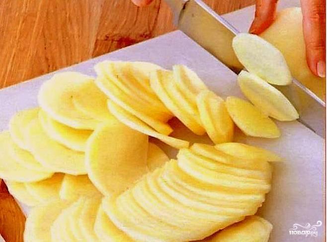 Нарезать картофель тонкими ломтиками примерно 2 миллиметра толщиной. Для этого лучше воспользоваться острым ножом или мандолиной.