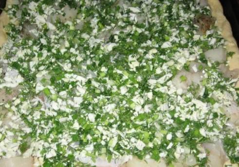 Подросшее тесто делим на две части - одна часть побольше, другая поменьше. Раскатываем ту часть, что побольше и укладываем ее на смазанный растительным маслом противень. Затем выкладываем слой рыбы, сверху яйца с луком и зеленью.