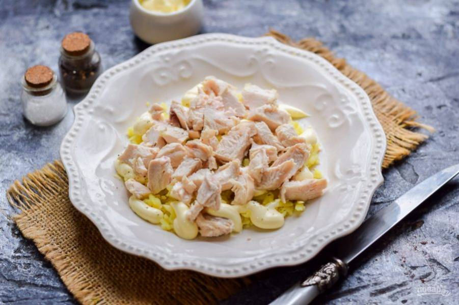 Отварное куриное филе нарежьте кусочками или разберите на волокна. Выложите филе поверх картофеля.