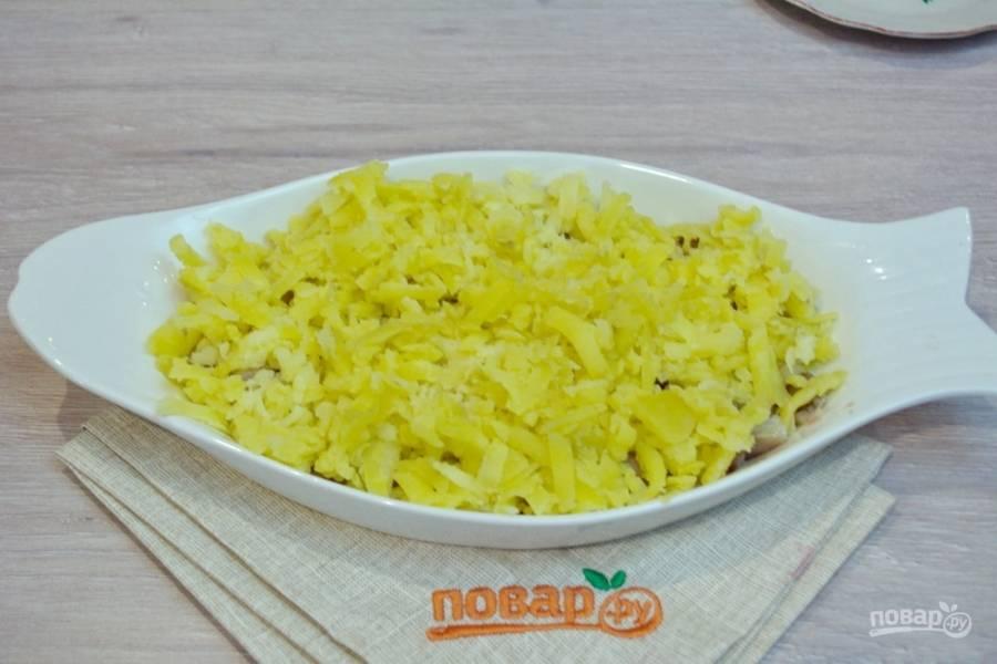 Отварной картофель очистите и натрите на крупной терке. Уложите слоем на селедку.