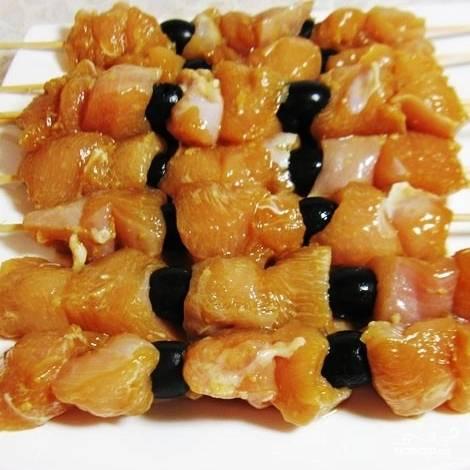 Затем на длинные шпажки нанизываем кусочки курицы и маслины.