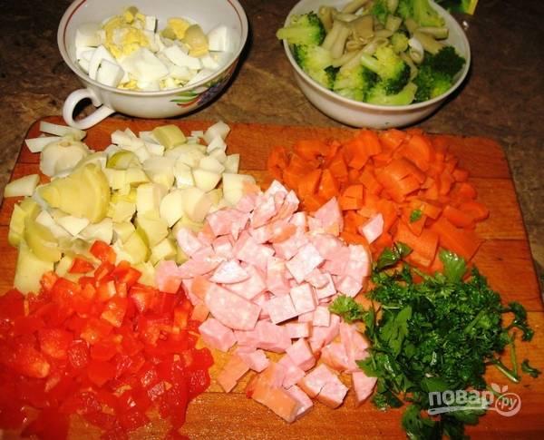 Нарежьте кубиками колбасу, перец, картофель, яйца и морковь. Петрушку мелко порубите. Брокколи разберите на соцветия. Фасоль разделите пополам.