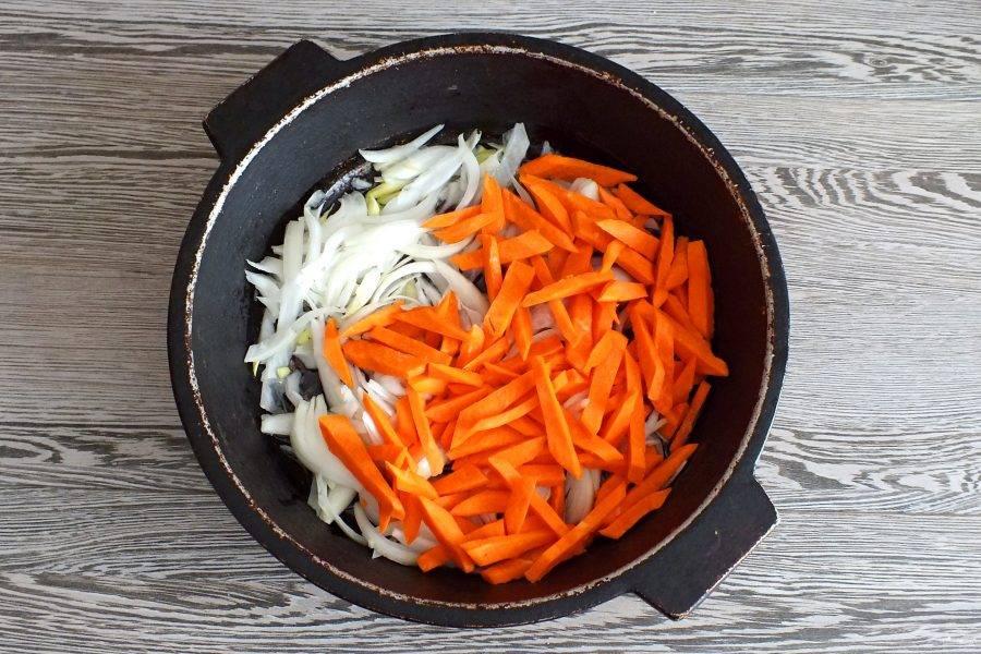 В жаровне или казанке раскалите растительное масло. Опустите в него лук и морковь. Обжаривайте, помешивая, до легкого румянца.