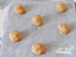 Скатайте из теста небольшие шарики. Выложите их на противень, предварительно застеленный бумагой для выпекания. Бумага нужна, чтобы печенье не прилипло к противню, так как  в нем очень высокое содержание сахара, который будет карамелизироваться в процессе запекания.