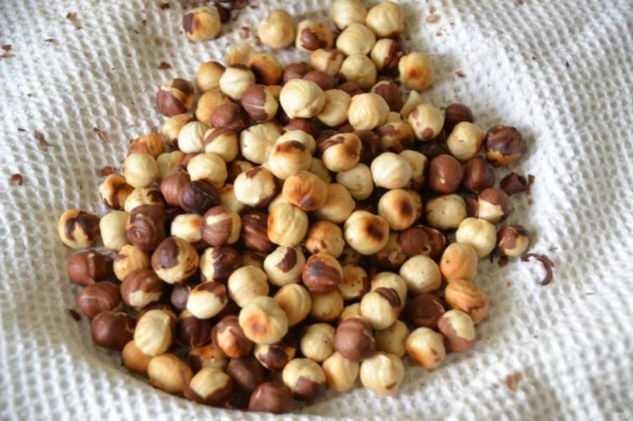 Высыпьте еще горячие орехи на вафельное полотенце, подхватите края полотенца в узел и перетрите орехи между собой, чтобы отделить шелуху. Если орехи очистятся на 70% это уже норма.