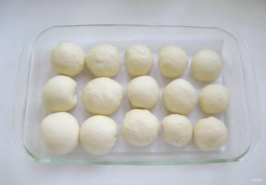 Таким образом приготовленные булочки выложите в форму для выпечки, застеленную пекарской бумагой.