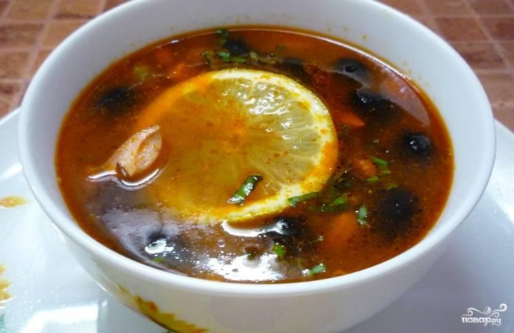 В конце добавьте растертый с солью чеснок для пикантности. Подавайте готовую солянку из зеленых помидоров с зеленью и лимоном. Готово!
