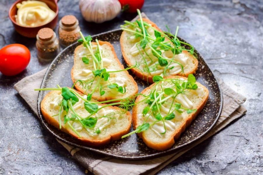 Ломтики батона смажьте сливочным сыром, поверх разложите микрозелень.