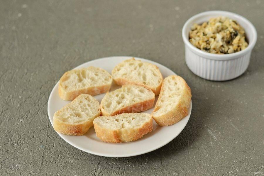 Нарежьте хлеб на ломтики средней толщины, сверху выложите начинку.