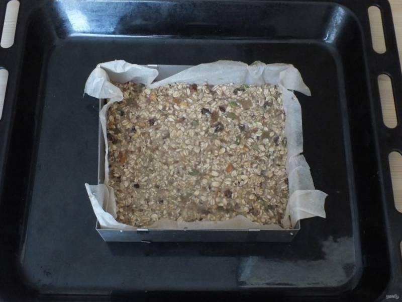 Возьмите прямоугольную форму, застелите пищевым пергаментом. Тонким слоем смажьте растительным маслом. Выложите овсяно-фруктовую массу, толщина должна быть не более 0,7 см. Утрамбуйте. И поставьте выпекаться на 30 минут в горячую духовку.