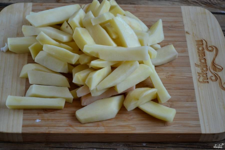 Картофель порежьте на дольки. Если картофель крупный, порежьте его соломкой.