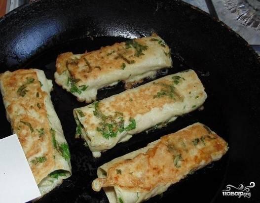 6. Для этого взбиваем яйцо и добавляем нашинкованную петрушку. Окунаем рулетики в заливку и обжариваем до румяного цвета на сливочном масле.