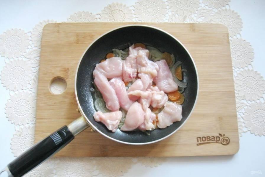 Затем куриное филе помойте, нарежьте и добавьте к моркови и луку.