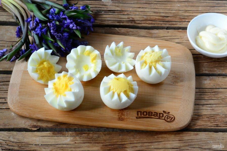 Яйца разрежьте пополам, прорезая край зубчиками, так, чтобы верхняя часть была немного меньше нижней. Это очень удобно делать кончиком тонкого ножа. Желток выньте, смешайте с майонезом, солью и специями по вкусу.