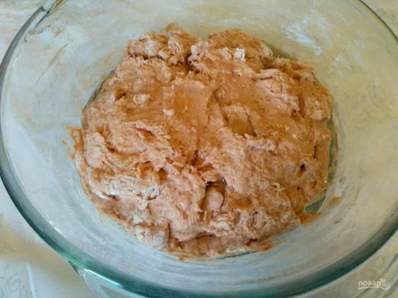 Когда тесто станет трудно мешать ложкой, влейте подсолнечное масло и завершите замес ручным способом, при необходимости добавляя муку из оставшегося количества.