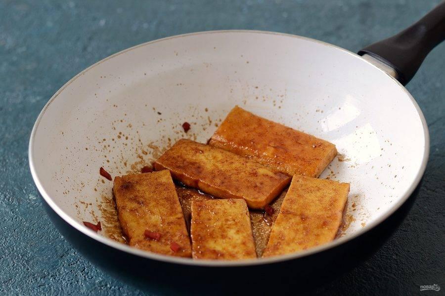Добавьте соевый соус и мелко порубленный перец чили. Обжарьте тофу с двух сторон до испарения жидкости.