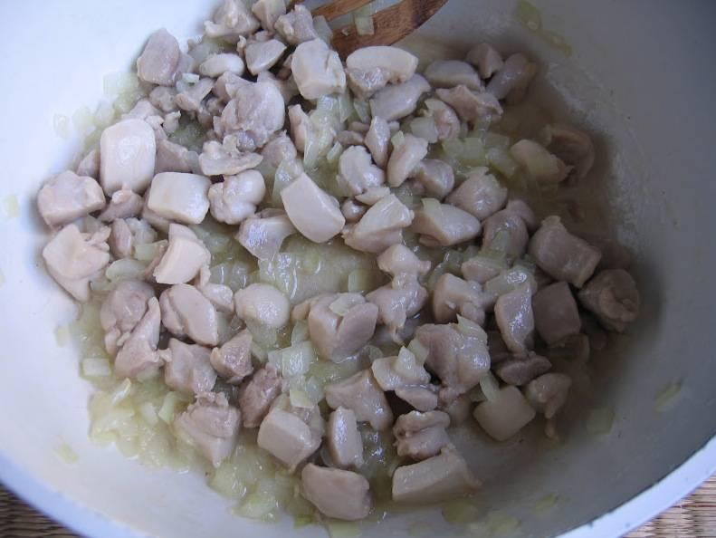 В кастрюле разогреваем оливковое масло. Добавляем курицу, жарим 2 минуты, после чего добавляем лук. Жарим, еще через 2 минуты добавляем морковь.