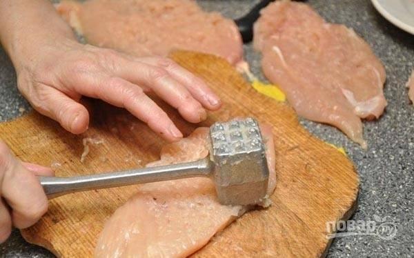Филе разрежьте на несколько больших кусочков. Отбейте его. Затем натрите куриное мясо солью и перцем.