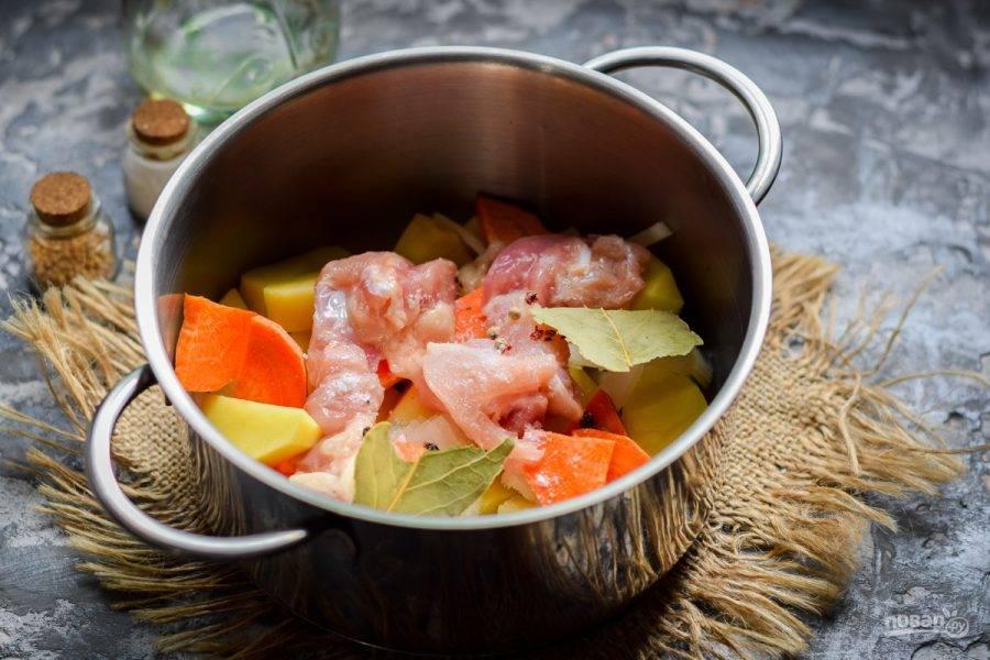 Куриное филе ополосните и крупно нарежьте, выложите филе в кастрюлю. Добавьте перец горошком, соль и лавровый лист.