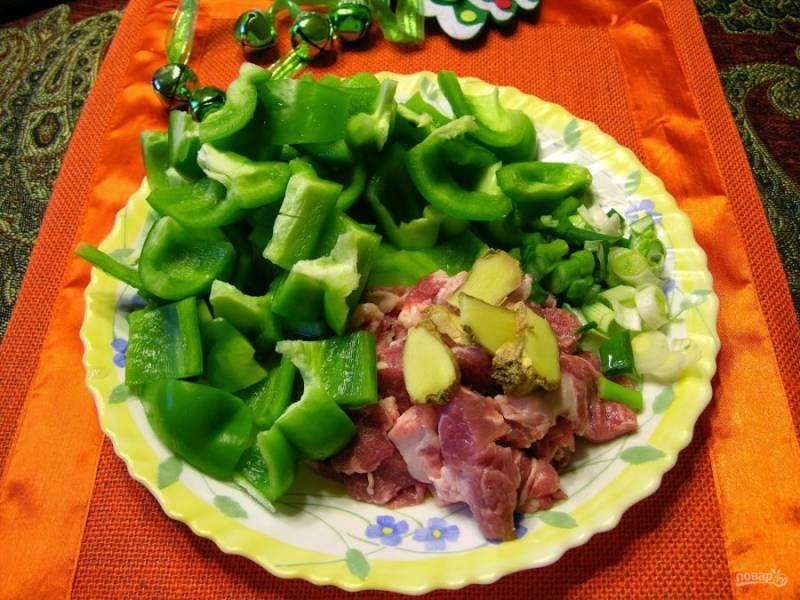 1.Сперва подготовьте все ингредиенты: вымойте мясо и нарежьте его кусочками. Вымойте имбирь и нарежьте небольшой корешок пластинками, очистите и нарежьте кусочками перец, измельчите зеленый лук.