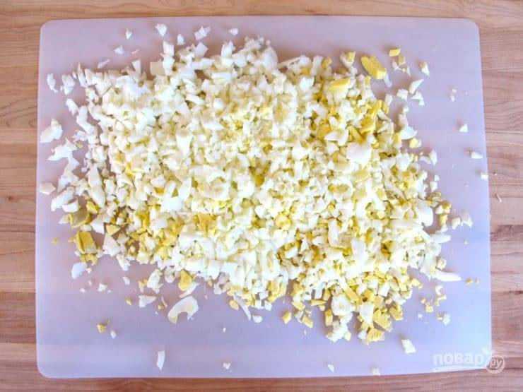 1. Заранее отварите вкрутую яйца и яичные белки. Затем их остудите, почистите и мелко нашинкуйте.