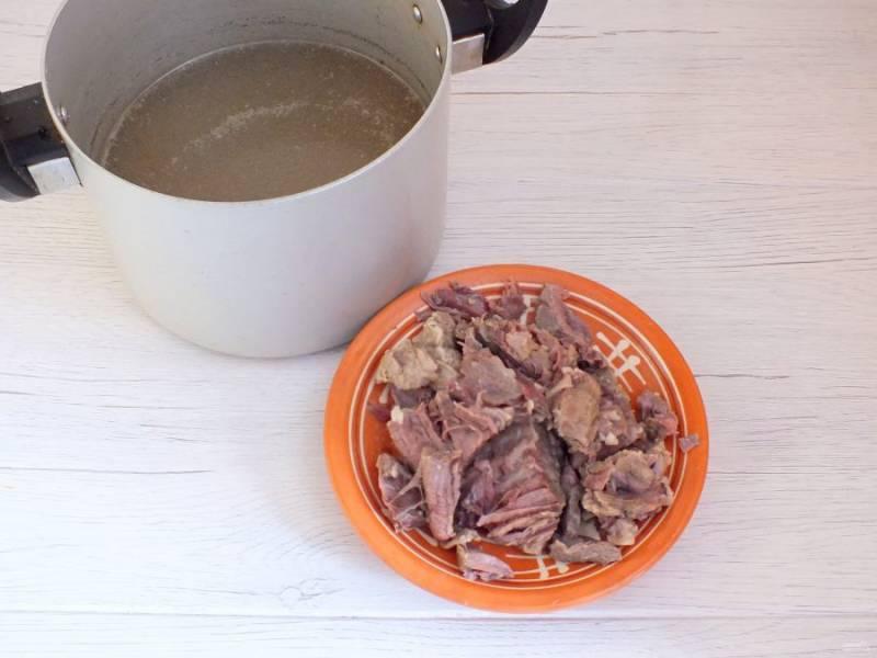 Говядину промойте. Выложите в кастрюлю, залейте кипятком и сварите бульон. Достаньте мясо из бульона. Удалите косточку. Мясо нарежьте на кусочки. Переложите его в бульон.
