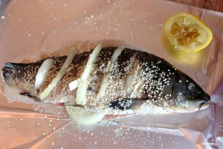 С обеих сторон сазана сделайте надрезы ножом. Порежьте полукольцами репчатый лук, вставьте его в надрезы и в брюхо рыбы. Посолите по вкусу, полейте сазана соком одного лимона и присыпьте кунжутом.