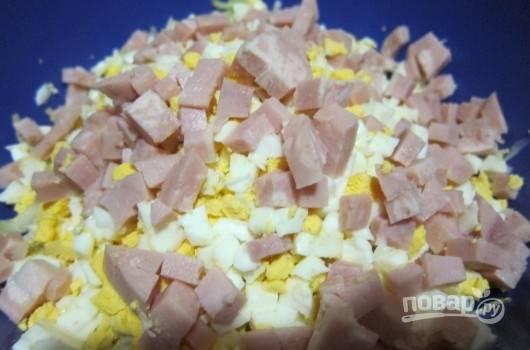 В миске смешайте яйца с капустой. Добавьте к ним ветчину, нарезанную кубиками.