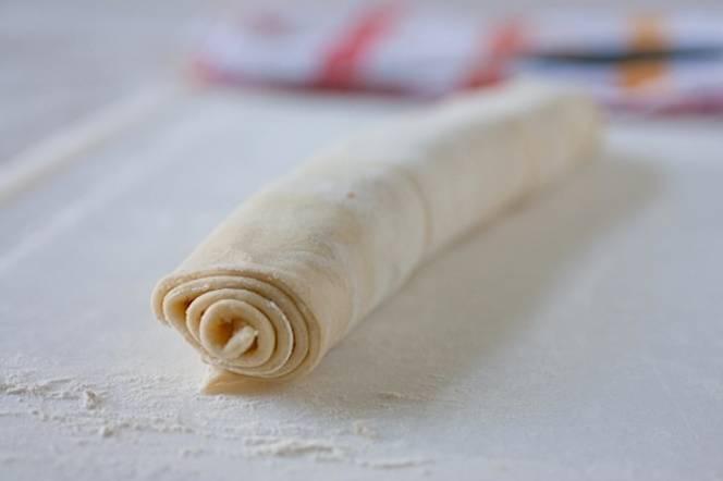 Теперь смазываем пласт теста растительным маслом, смешанным с мукой. Сворачиваем тесто в рулет и кладем в холодильник на 25 минут.