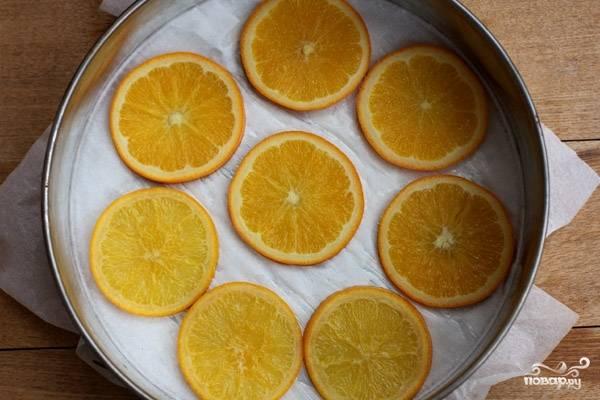 2. Подготовьте форму для выпечки диаметром 20 см. Дно формы застелите пергаментом, а бока смажьте маслом. Дольки апельсина достаньте из сиропа и просушите бумажным полотенцем. Часть апельсинов красиво разложите на дне формы.