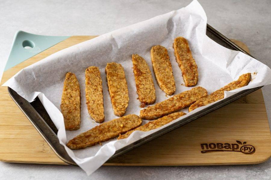 Разогрейте духовку до 180 градусов. Выложите темпе в один слой на пергамент, смажьте растительным маслом и запекайте 20 минут. Во время приготовления их можно перевернуть 1 раз.