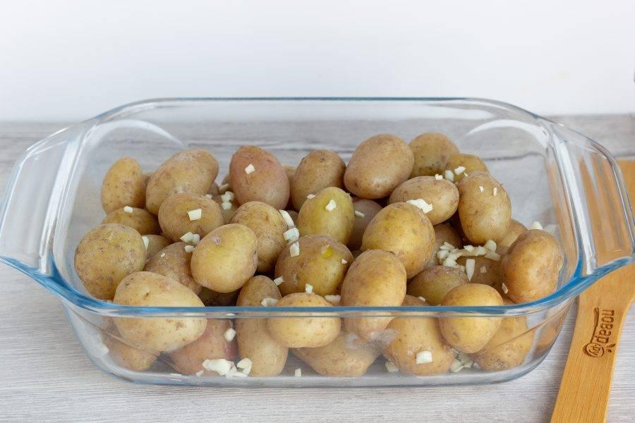 Выложите картофель в форму для запекания и добавьте рубленный чеснок. Посолите и поперчите по вкусу.