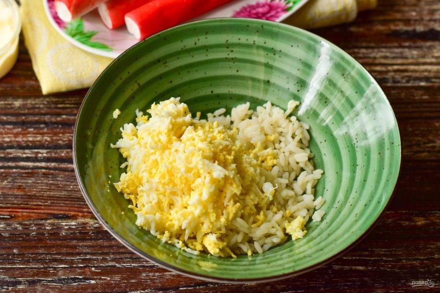 В глубокую миску выложите вареный рис. К нему натрите на мелкой терке вареные куриные яйца.