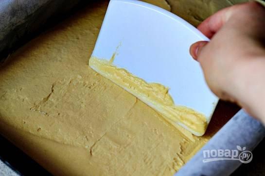 На застеленный пергаментной бумагой противень вылейте тесто и аккуратно разровняйте.