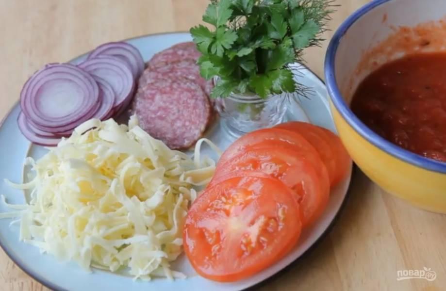 1.Подготовьте все необходимые ингредиенты. Овощи и колбасу нарежьте, сыр натрите, измельчите зелень.