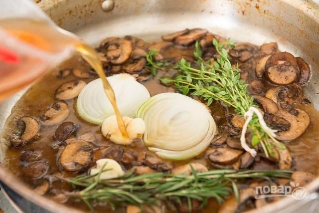 7. Потом влейте бульон. Добавьте раздавленный чеснок, лук кольцами и травы.