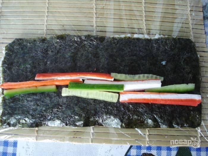 Затем рис переверните вниз. Нарежьте брусками огурец и крабовые палочки. Выложите их кусочки на нори.
