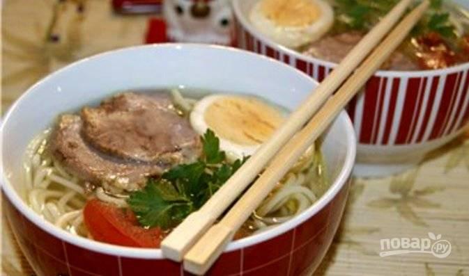 Соберите суп. В каждую тарелку уложите лапшу. Залейте её бульоном. Сверху уложите порезанное мясо тясю и половинку яйца. Украсьте по своему вкусу. Приятного аппетита!