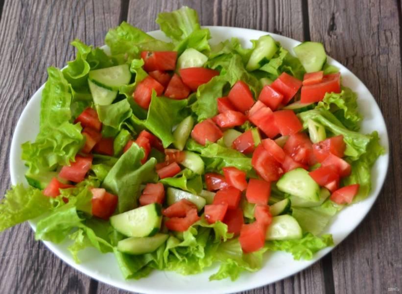 Нарежьте помидор кубиками, выложите сверху на огурцы.