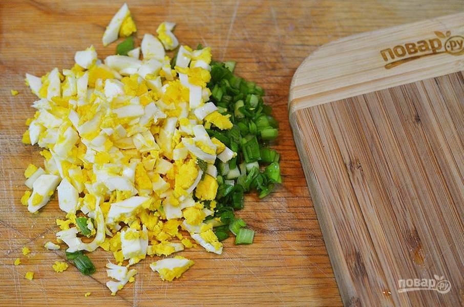 Пока тесто настаивается, сделаем начинку. Лук и яйца мелко нарежьте.