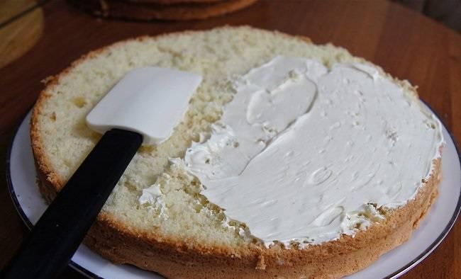 6. Для приготовления крема необходимо соединить желтки двух яиц с водой и слегка взбить. Добавить сгущенку и отправить на медленный огонь или водяную баню. Крем нужно уварить до загустения. Тем временем взбить сливочное масло. При желании в масло можно добавить ванильный сахар или эссенцию. Соединить уваренный крем с маслом и тщательно взбить. Готовым кремом смазать коржи.